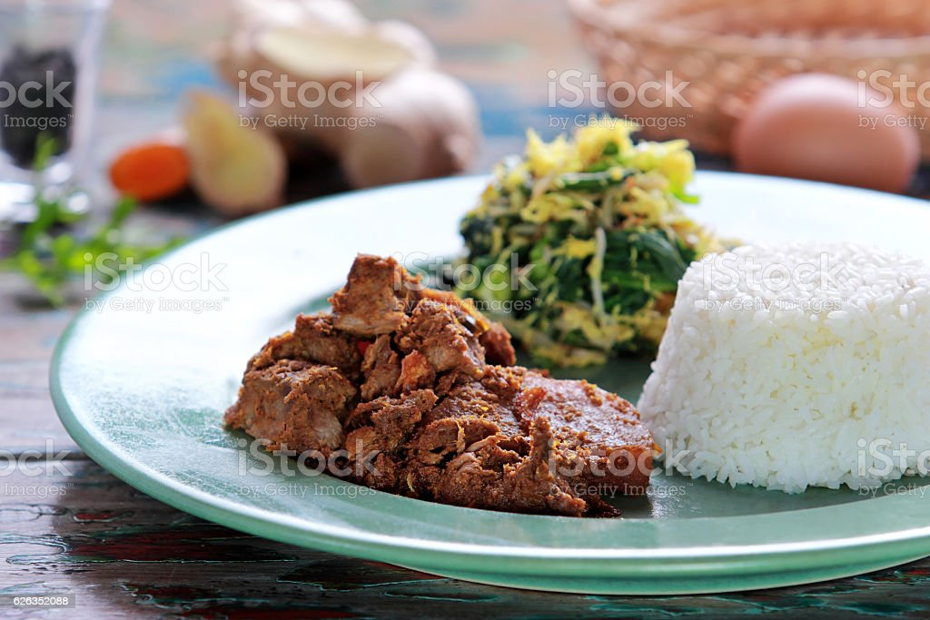 beef rendang served with urap and rice stock photo