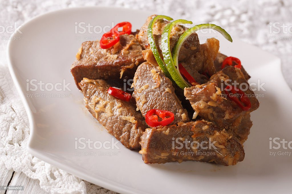 Beef rendang stewed in coconut milk with spices close-up. Horizontal stock photo