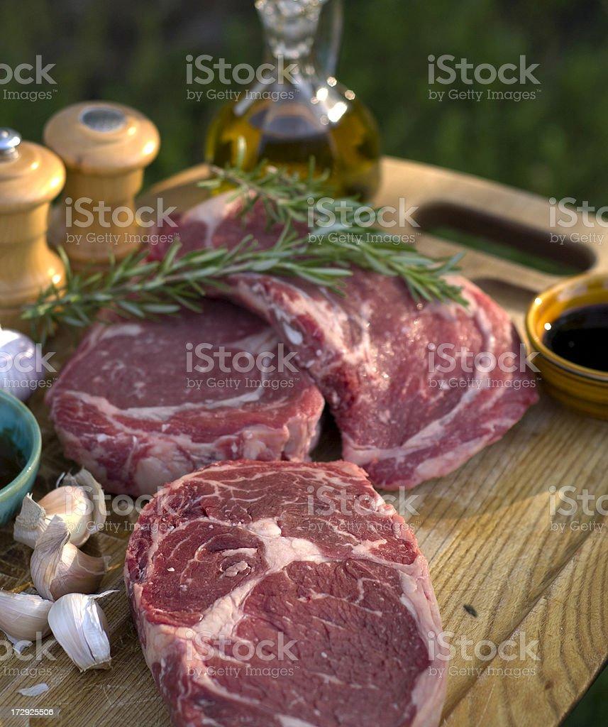 Beef Rib Eye Raw Steak Cooking Dinner Preparation, Rosemary & Peppercorns royalty-free stock photo