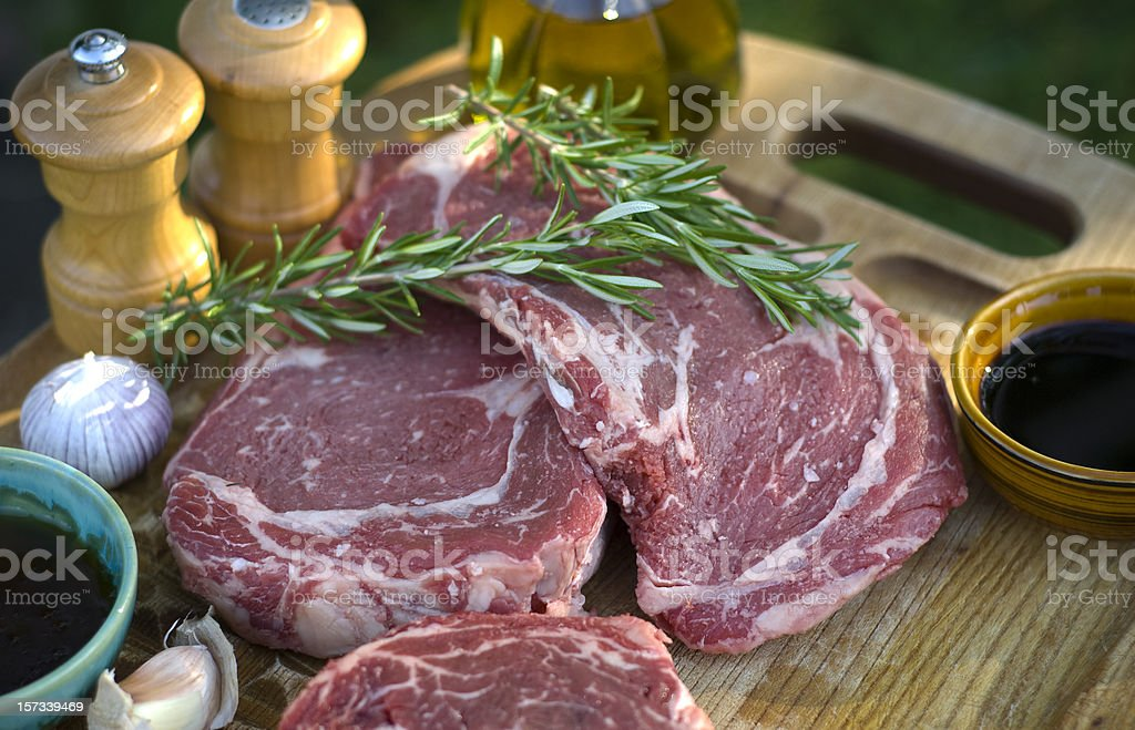 Beef Rib Eye Steaks, Fresh Raw Meat Marinade & Barbeque Cooking royalty-free stock photo
