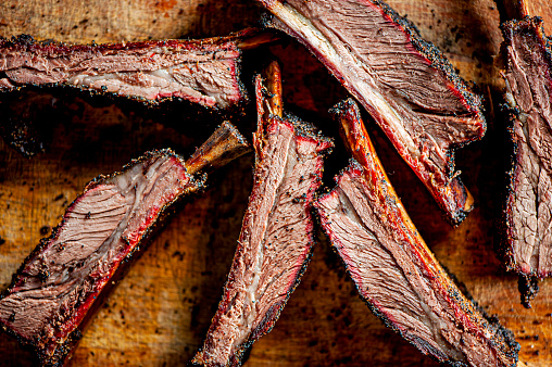 Beef ribs. Barbecue table spread. Beef brisket, chicken, pork ribs, beef ribs, Mac n cheese, cornbread, Brussels sprouts, coleslaw & beer. Classic traditional Texas meats & side dishes.