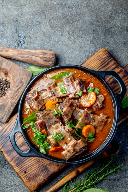 Beef ribs Bourguignon. Beef ribs stewed with carrot, onion in red wine. France dish. Top view. Copy space Bourguignon beef ribs stewed with onion, carrot in red wine. Top view beef bourguignon stock pictures, royalty-free photos & images