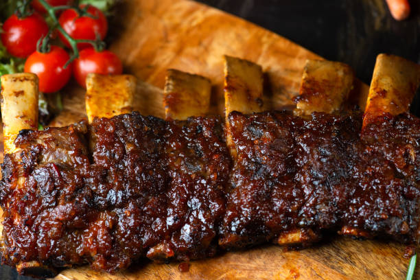 Bife dos reforços da carne do BBQ serido com uma pimenta de pimentão quente e tomates frescos em uma placa de estaca de madeira do vintage velho - foto de acervo