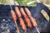 Beef sausages grilled on a coals. Barbecue on brazier.