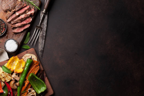 rindersteak und grillgemüse auf schneidebrett - grillstein stock-fotos und bilder