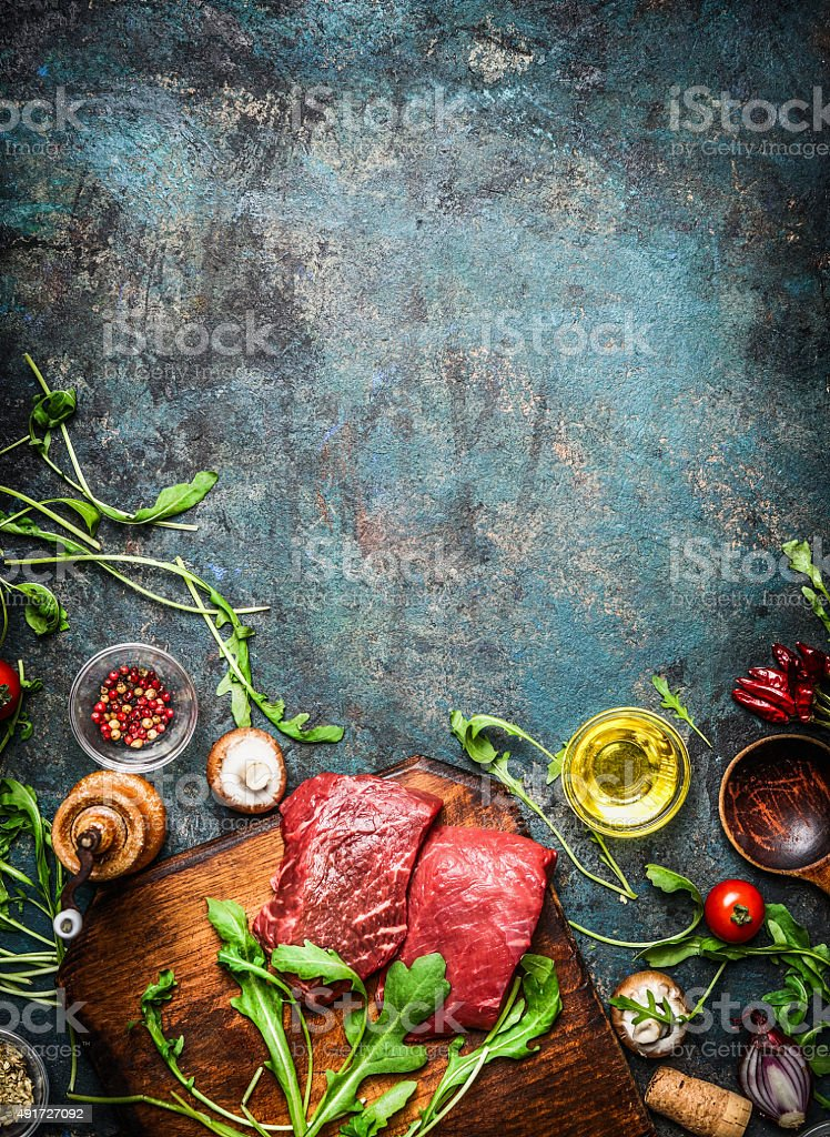 Beef steak and various ingredients for cooking on rustic background stock photo