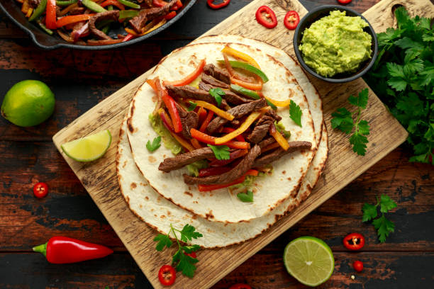 Beef Steak Fajitas with tortilla mix pepper, onion and avocado on wooden board stock photo