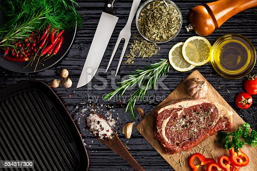 Top view of a kitchen table with a wooden cutting board with beef steak fillet ready for cooking. Beside the cutting board are some spices and ingredients for cooking and seasoning. DSRL studio photo taken with Canon EOS 5D Mk II and Canon EF 100mm f/2.8L Macro IS USM