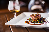 Beef Steak. Grill beef steak black lentils mixed with vegetable. Cognac or brandy as drink. Culinary food in hotel pub or restaurant.
