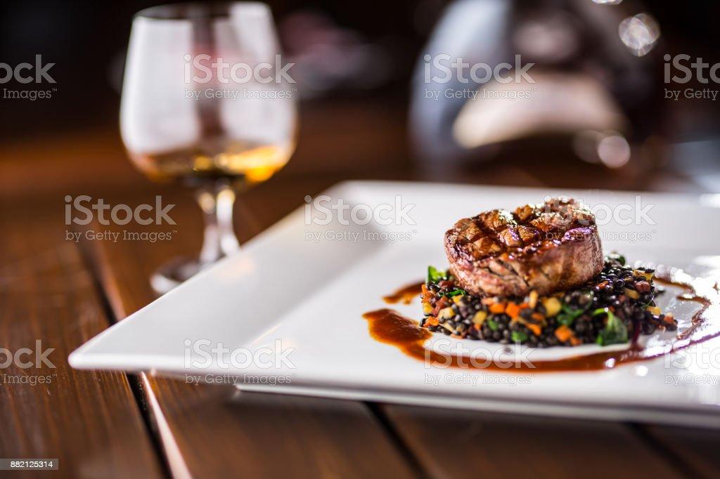 Rindersteak. Grill Beefsteak schwarze Linsen mit Gemüse gemischt. Cognac oder Weinbrand als Getränk. Kulinarische Speisen im Hotel-Pub oder restaurant – Foto