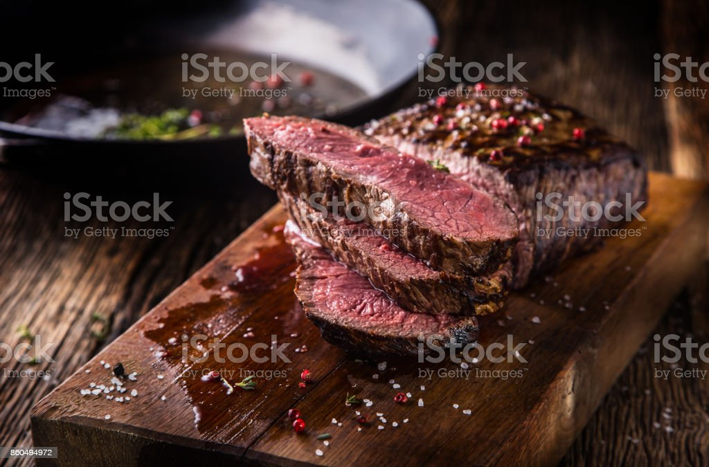 Beef steak. Juicy medium Rib Eye steak slices on wooden board with fork and knife herbs spices and salt stock photo
