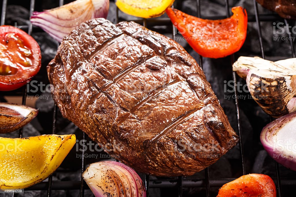 Beef steak on a barbecue grill with vegetables stock photo