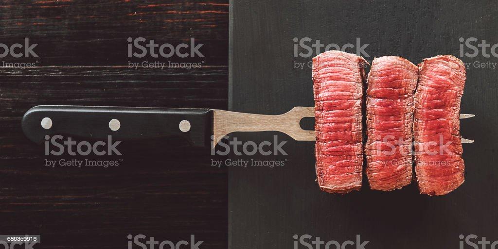 beef steak on a fork on a dark wooden background stock photo