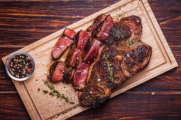 beef steak auf einem hölzernen hintergrund - steak anbraten stock-fotos und bilder