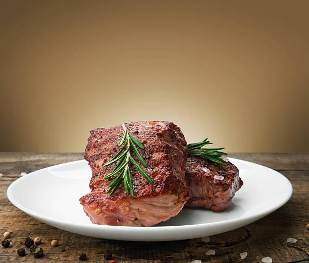 beef steak on a wooden table - vleesdelen stockfoto's en -beelden