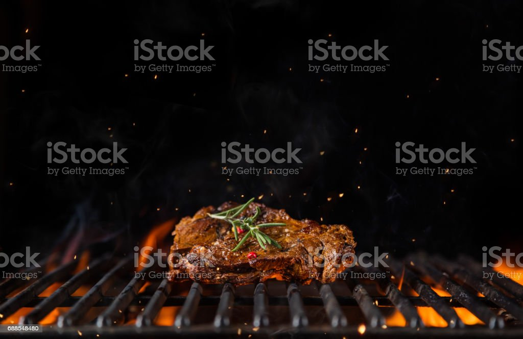Beef steak on the grill grate, flames on background stock photo