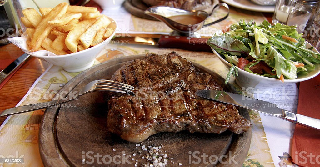 Beef Steak on wooden plate with chips and salad royalty-free stock photo