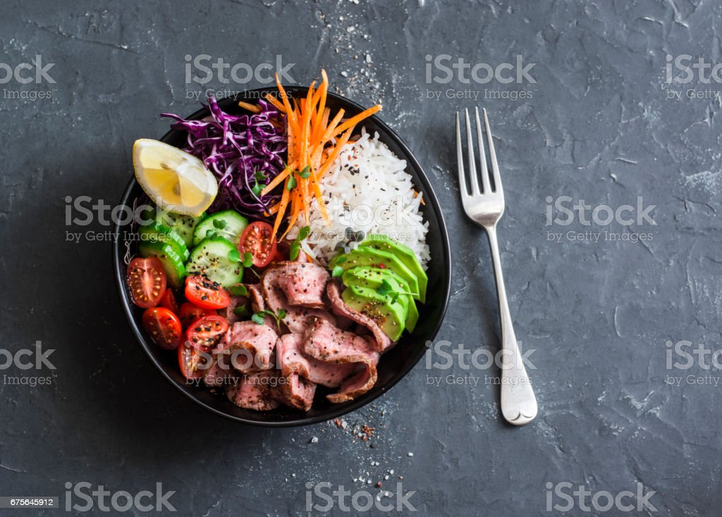 Beef steak, rice and vegetable power bowl. Healthy balanced food concept. On a dark background, top view royalty-free stock photo