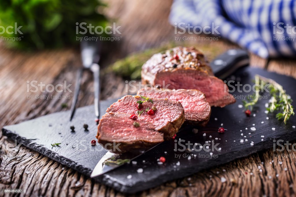 Beef Steak. Roasted Beef steak with salt pepper thyme on rustic wooden table stock photo