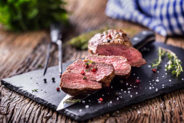beef steak. roasted beef steak with salt pepper thyme on rustic wooden table - beef stock pictures, royalty-free photos & images