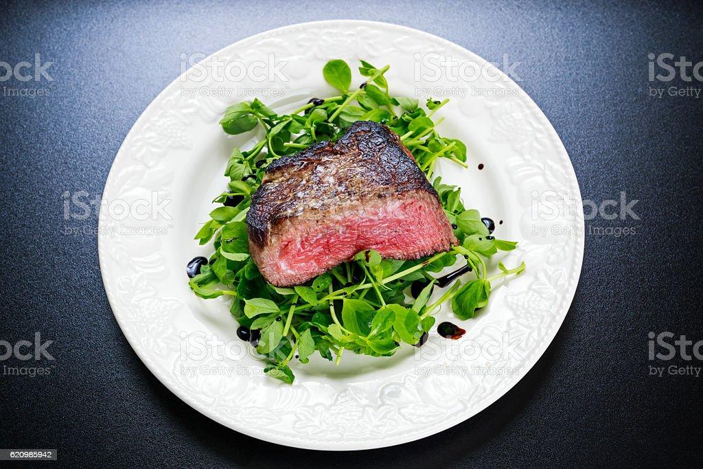 Filé-Mignon de carne bovina fatiada com salada. Servido sobre prato branco foto royalty-free