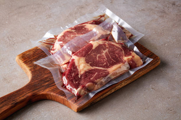 biefstuk vacuüm verzegelde op stenen tafel - vleesdelen stockfoto's en -beelden