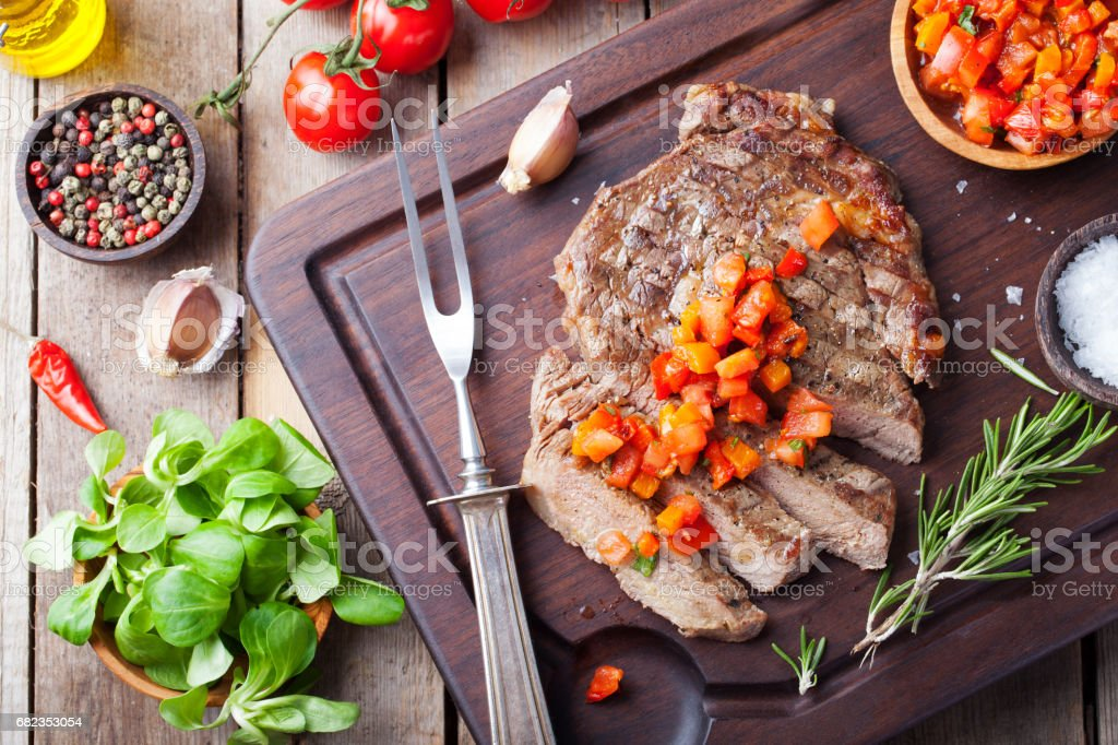 Beef steak well done with tomato and pepper salsa on a wooden background foto stock royalty-free