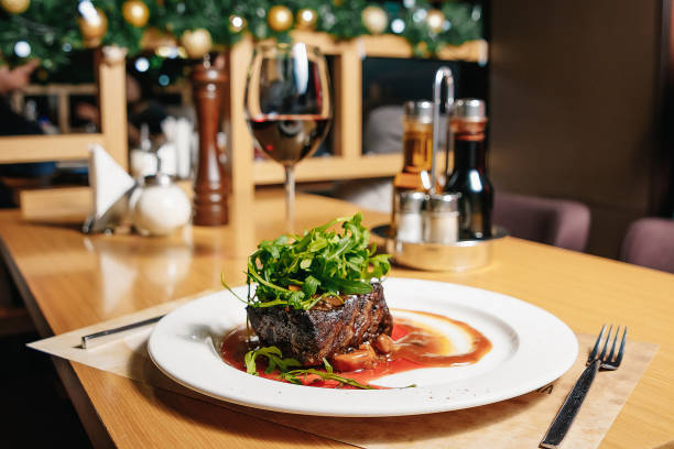 beef steak with arugula and champignons on a white plate on the table in the restaurant. a glass of red wine, a salt, a pepper. - raw steak imagens e fotografias de stock