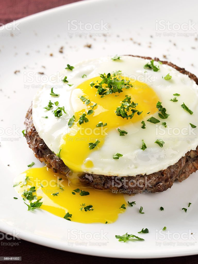 Beef Steak with fried egg on white plate stock photo