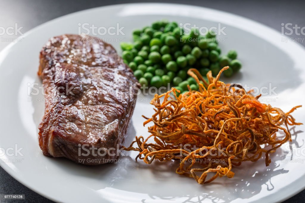 Beef steak with green peas and sweet potato stock photo
