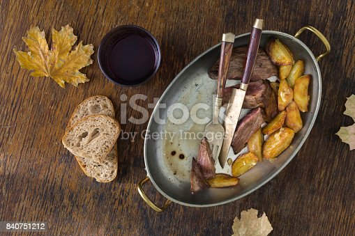 808351132 istock photo Beef steak with potatoes in garlic sauce in a frying pan on a wooden table with a glass of red wine 840751212