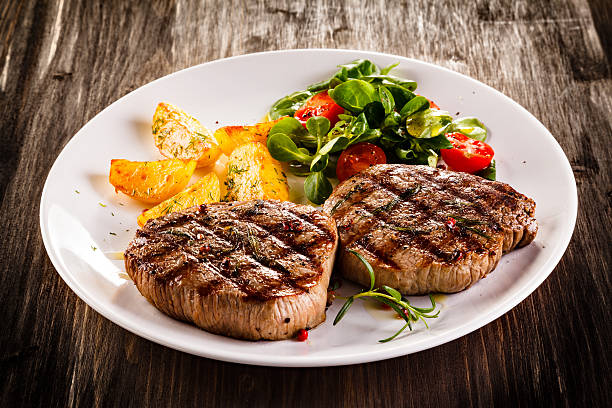 bifes de carne de bovino, batatas assadas e salada de vegetais - meat plate imagens e fotografias de stock
