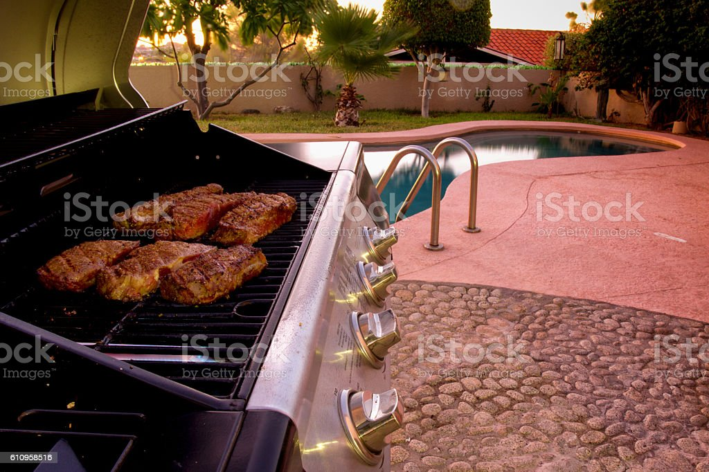 Beef Steaks on a Grill Next to a Swimming Pool stock photo