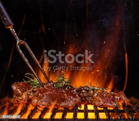 istock Beef steaks on the grill grate, flames on background 688548866