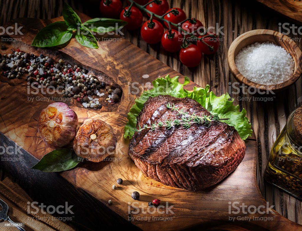 Beef steaks with spices on a wooden tray. stock photo