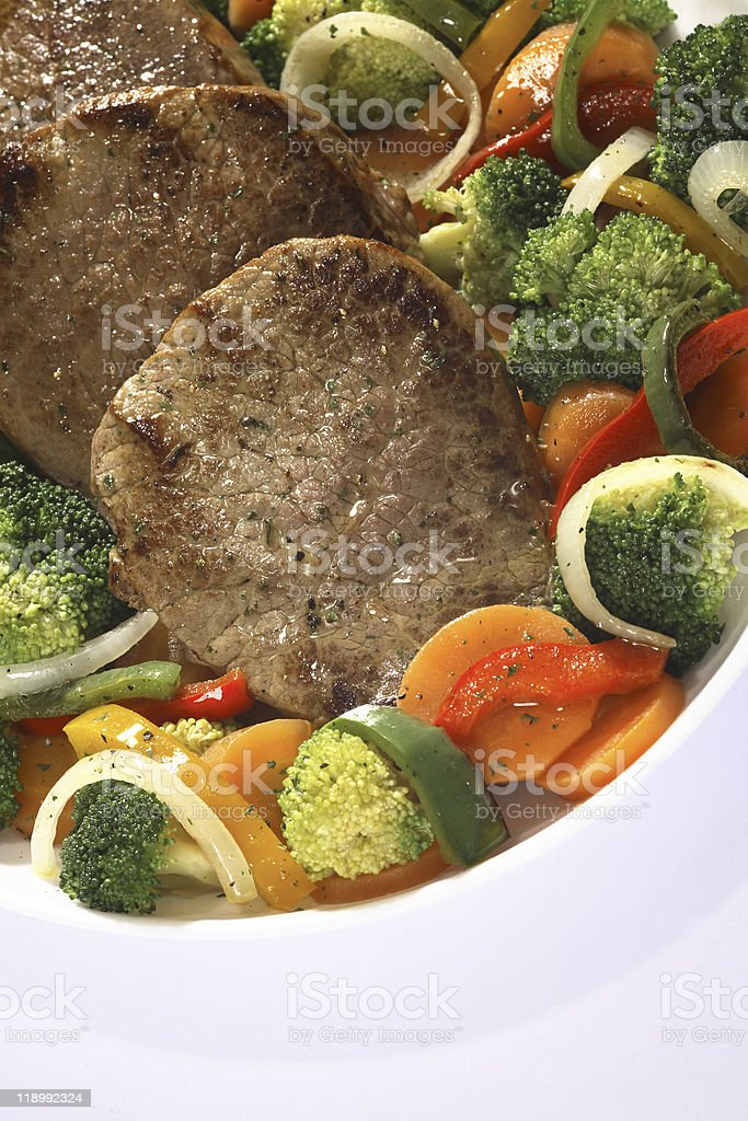 beef steaks with vegetables in serving dish royalty-free stock photo