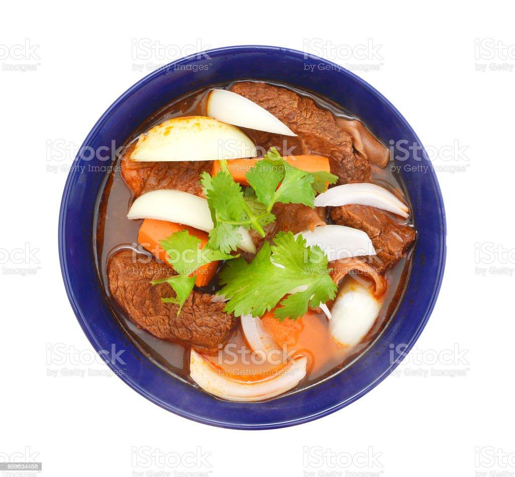 guiso de carne y verduras en un tazón azul sobre fondo blanco - Foto de stock de Alimento libre de derechos