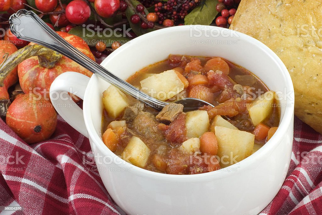 Beef stew in a mug with metal spoon in plaid washcloth royalty-free stock photo