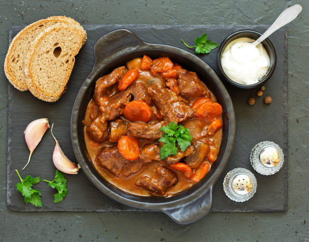Beef stew in Burgundy. With carrots, onions, peas and champignons in wine. View from above. stock photo