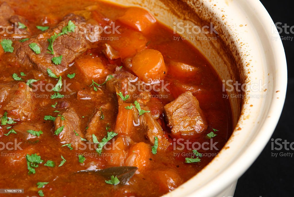 Beef stew in white crockpot with black background stock photo