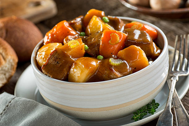 Beef Stew A delicious bowl of rich and hearty beef stew with potato, turnip, carrot, celery, and peas. beef stew stock pictures, royalty-free photos & images