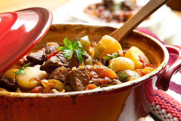 Beef Stew Traditional goulash or beef stew, in red crock pot, ready to serve.  Shallow DOF.  More beef images: goulash stock pictures, royalty-free photos & images