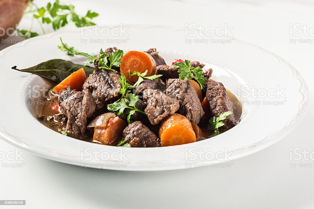 Beef stew with carrot on white. Selective focus. stock photo