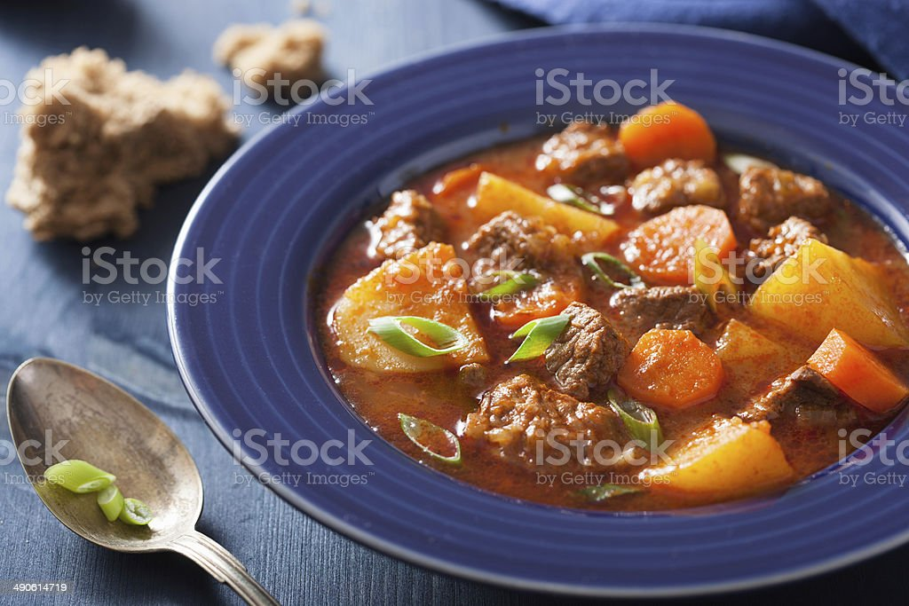 beef stew with potato and carrot in blue plate stock photo