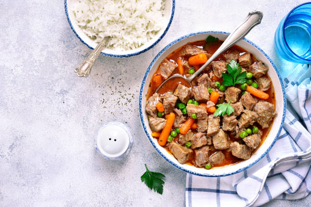 Beef stew with vegetables garnished with boiled rice Beef stew with vegetables garnished with boiled rice in a vintage bowl over light slate, stone or concrete background.Top view. ragout stock pictures, royalty-free photos & images