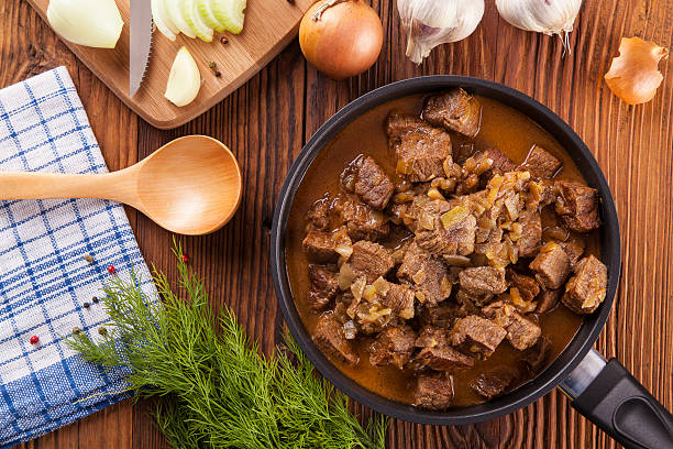 beef stew - wooden background - meat pan stockfoto's en -beelden