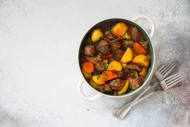 Beef stewed with vegetables on a stone  background Beef stewed with vegetables on a stone  background. Flat lay. Copy space beef stew stock pictures, royalty-free photos & images