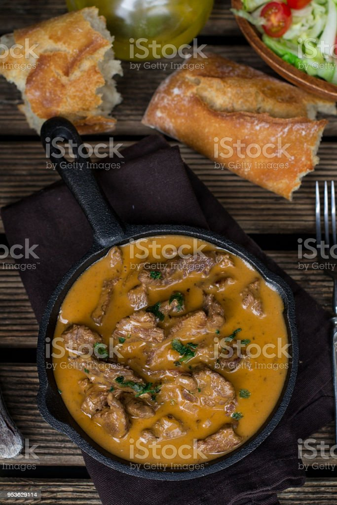 Beef stroganoff in sauce with sour cream and tomato with bread stock photo