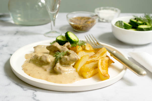 rundvlees stroganoff traditionele russische schotel van rundvlees in saus, geserveerd met gebakken aardappelen, ingeblikte komkommers, wodka. - zout smaakstof stockfoto's en -beelden