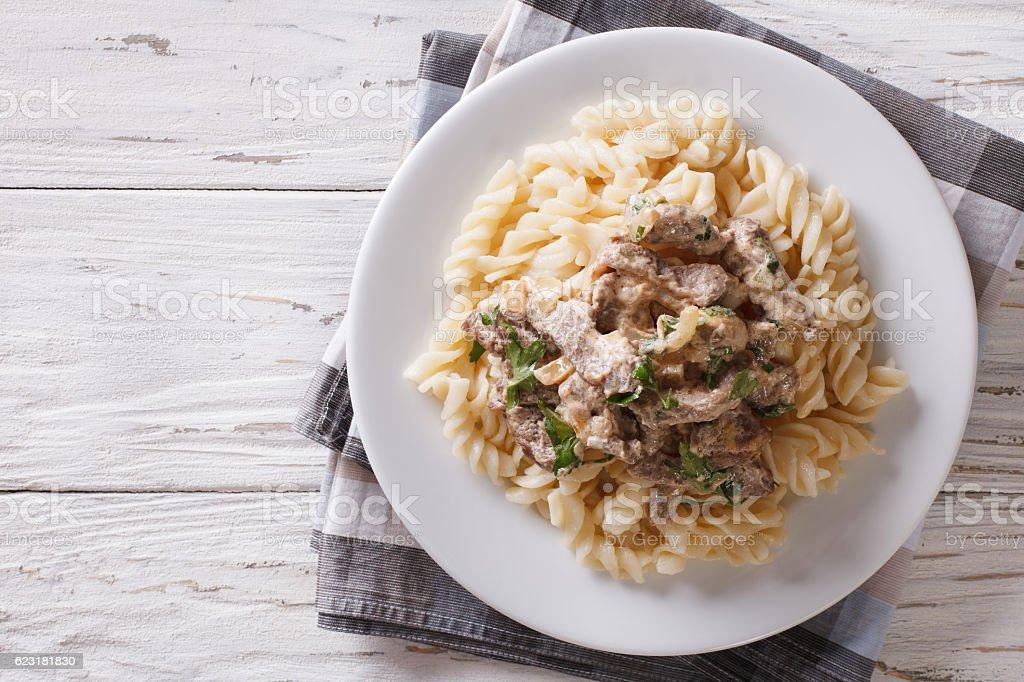 beef stroganoff with pasta fusilli . Horizontal top view stock photo